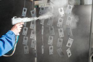 Man powder coating objects in Australia