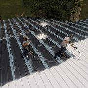 Roof paint being applied by a professional roof painting service
