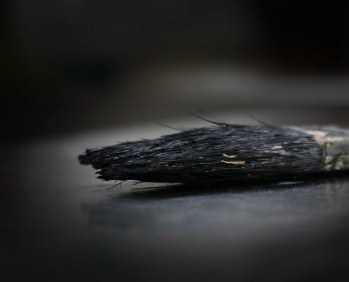 black liquid rubber paint on a paint brush