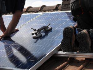applying solar panel coating on roof panels
